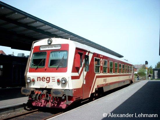 Der Triebwagen der neg Norddeutsche Eisenbahngesellschaft Niebüll mbH steht im Auftrag der Nord-Ostsee-Bahn, dessen Schienenbus an diesem Tage nicht einsatzbereit war, im dänischen Bahnhof Toender am Hausbahnsteig zur Rückfahrt Ri. Niebüll bereit (KBS 136.1). Der Triebwagen (Bj. 1995) ist ein Prototyp der für die Österreichische Bundesbahn (ÖBB) in Auftrag gegangenen Dieseltriebwagen. Das Bild entstand Himmelfahrt 2005 (5.5.05).