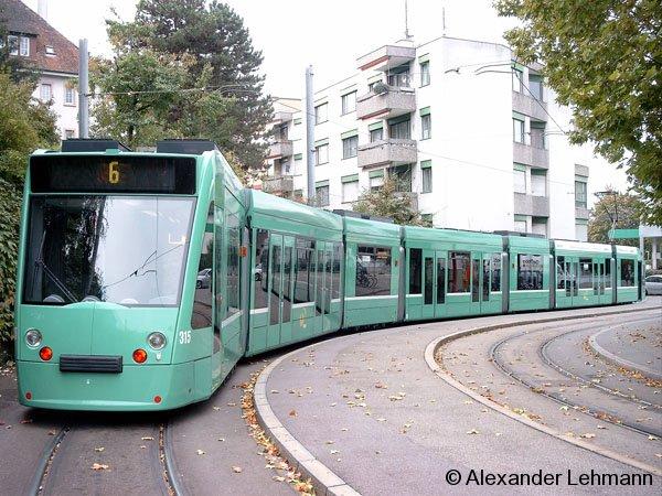 Ein siebenteiliger Combino auf der Straßenbahnlinie 6 liegt in Basel (CH) in der Kehre der Hst.