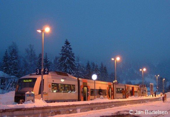 Im winterlich verschneiten und abendlichen Bayrischzell wartet ein Triebwagen vom Typ