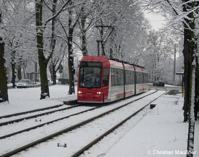 Straßenbahnzug 1107 hat am 12.12.2008 im verschneiten Nürnberg gerade die Haltestelle Am Rangierbahnhof verlassen.