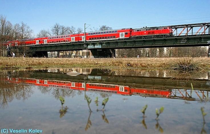 Am 28.03.2009 passiert eine Lokomotive der Reihe 218 mit einem Doppelstockzug die Braunauer Brücke über die Isar in München. Der Zug ist nach Mühldorf unterwegs. Für die Spiegelung nutze der Fotograf eine Pfütze mitten auf der Wiese.