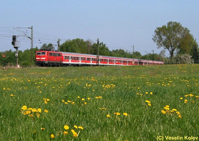 Nahe Ostermünchen entstand am 3.05.2009 dieses Aufnahme von einer Lok der Reihe 111 samt ihrem Regionalzug, der aus München kommend in Richtung Salzburg unterwegs ist.