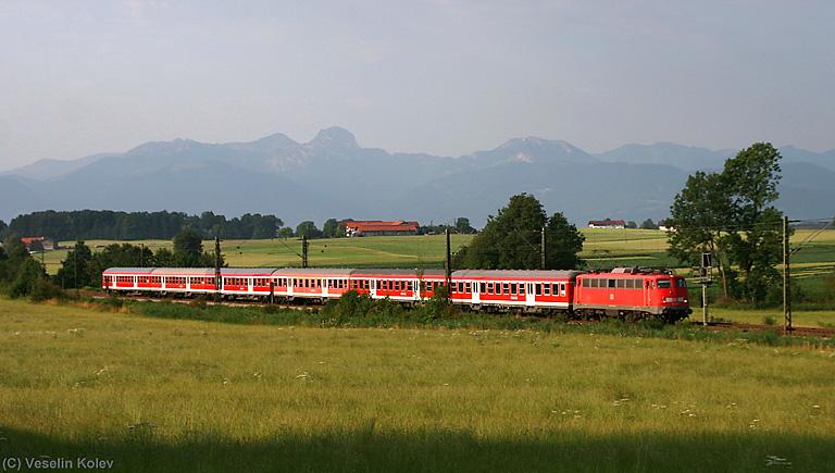 Eine Bügelfaltenlok der Reihe 110 hat am Morgen des 14.07.2009 einen Pendlerzug von Kufstein nach München am Haken. Zwischen Großkarolinenfeld und Ostermünchen wurde das Ganze samt Alpen im Hintergrund aufgenommen.