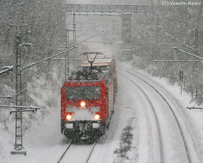 Durch die verschneite bayerische Landeshauptstadt ist eine Lok der Reihe 185 am 21.12.2009 mit einem Containerzug unterwegs. Die Aufnahme entstand am Nockherberg zwischen München Hbf und München Ost.