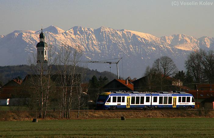 Ein LINT-Triebwagen der Bayerischen Regiobahn durchfährt am 7.04.2010 die Ortschaft Wielenbach in Richtung Weilheim. Noch sind Alpengipfel im Hintergrund tief verschneit.