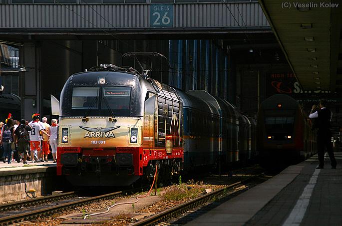 Dies ist 183 001, die neue Werbelok von Arriva zum 175. Jubiläum der Eisenbahn in Deutschland. Die Aufnahme entstand am 27.06.2010 im Münchner Hauptbahnhof; links im Bild sind deutsche Fußballfans zu sehen, die sich in der Innenstadt versammeln werden und später den deutschen Sieg über England feiern werden.