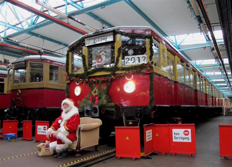 Bereits im zweiten Jahr in Folge kann der Weihnachtszug der Berliner S-Bahn nicht eingesetzt werden. Das Bild zeigt Zug und Personal daher wartend in der Triebwagenhalle Erkner anlässlich eines von der S-Bahn GmbH und der Historischen S-Bahn e.V. am 28.11.2010 veranstalteten Weihnachtsmarktes. Die Führerstandsfront von 475 605-2 wurde auch ohne Fahrten in diesem Jahr für die Veranstaltung weihnachtlich geschmückt. Die Jahresangabe im Führerstandsfenster zeigt