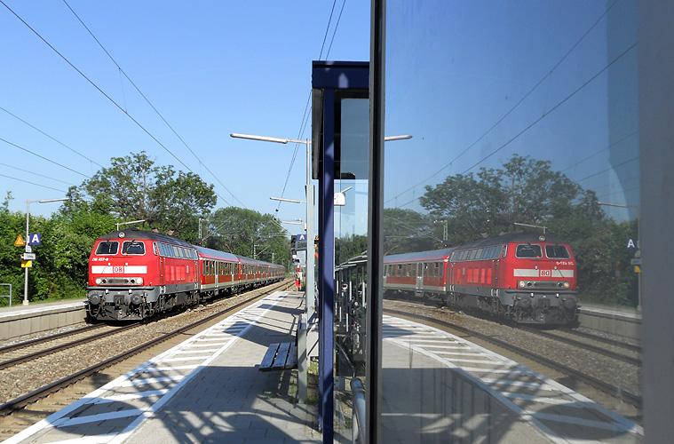 218 457 spiegelt sich am 25.05.2011 bei der Durchfahrt des Haltepunkts Eichenau.