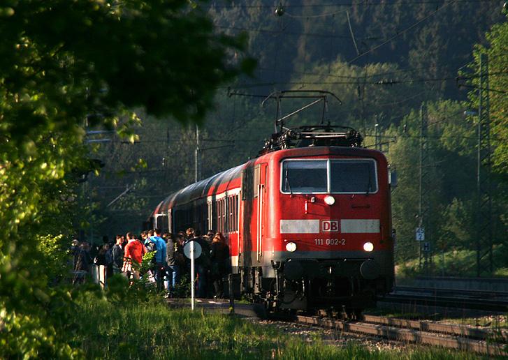 111 002 hält mit einem gut besetzten Pendlerzug am 6.05.2011 in Aßling.