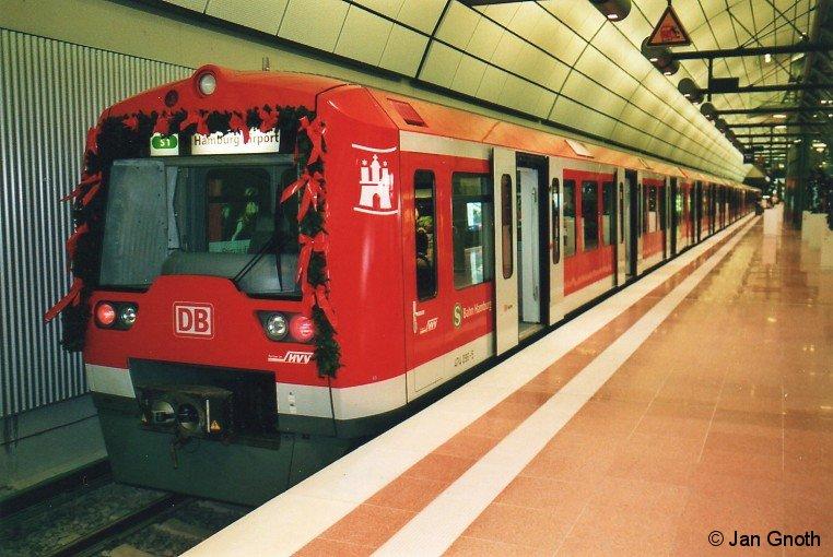 Seit 11. Dezember 2008 ist der Hamburger Flughafen - welcher mit einem großen Volksfest am Wochenende 24./25. September 2011 sein 100jähriges Bestehen feiert - mit der Gleichstrom-S-Bahn zu erreichen. In seiner 100jährigen Geschichte war der Hamburger Flughafen mit mehreren Systemen an den städtischen Nahverkehr angebunden: Von 1926 bis 1974 mit den Straßenbahnlinien 28 und 9, von 1983 bis 2008 mit der Buslinie 110. Das Bild zeigt den aus 474 096+098 bestehenden Eröffnungszug, welcher während der Eröffnungsfeier am 11. Dezember 2008 im Flughafenbahnhof abgestellt war.