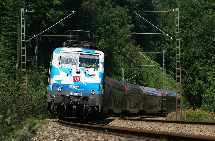 In der Mittagshitze des 23.08.2011 ist Bahnland Bayern-Lok 111 017 mit einem Regionalzug von München nach Salzburg unterwegs, aufgenommen zwischen Grafing und Aßling.