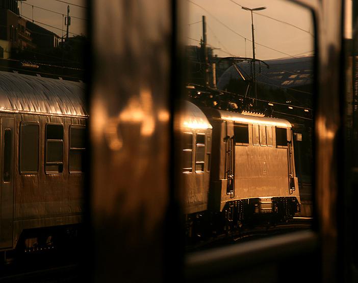 Abendstimmung am Münchner Hauptbahnhof: 111er mit Regionalzug nach Mittenwald spiegelt sich in den Regionalzug nach Füssen, aufgenommen am 16.09.2011.
