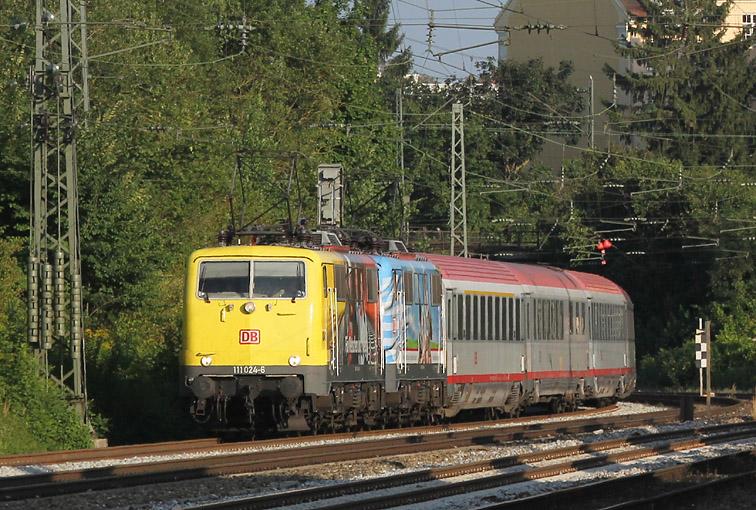 Weil es Spaß macht: Am 11.08.2012 waren einige EC-Züge von München zum Brenner und zurück sehr bunt bespannt. Im Bild 111 024 und 111 066 am Heimeranplatz.