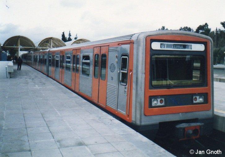 Eine kleine Impression von der Athener Elektrikos: Ein MAN/LEW-Zug der 1. Serie (erkennbar an den Klappfenstern, 2. Serie hat Übersetzfenster) als HVZ-Verstärker während der Kurzkehre auf dem mittleren Gleis in Eirini. Der Bahnhof Eirini hat 3 Bahnsteiggleise: Die beiden äußeren Gleise sind für die Stammzüge von und nach Kifissia, auf dem mittleren Gleis kehren die HVZ-Verstärker zur Rückfahrt nach Peiraia.