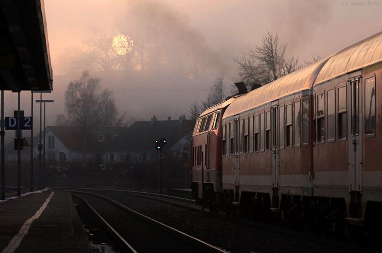 Abfahrt in den dunstigen Abend hinein - ein Regionalexpresszug verlässt am 12.12.2013 Kaufbeuren in Richtung Füssen