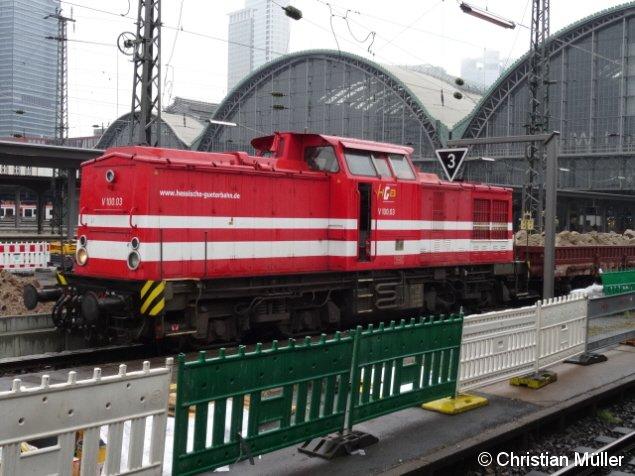 Verbrennungslok V100.03 der Hessischen Güterbahn in Frankfurt am Main Hbf. Dieser Flachwagenzug hat am Donnerstag den 18. Juni Abraum eines zu modernisierenden Bahnsteigs abtransportiert.