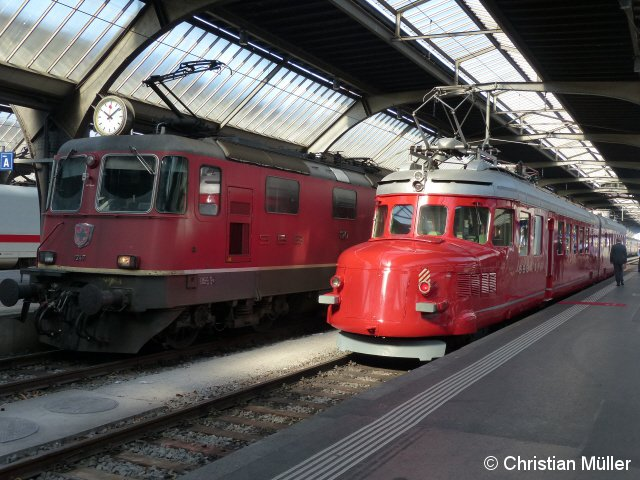 Vom Sonnenlicht erhellt steht am Hauptbahnhof in Zürich ein roter Doppelpfeil (Churchill-Pfeil) neben der Elektrolok 11247 zur Abfahrt bereit. Die Aufnahme entstand am So, den 10.4.2016.