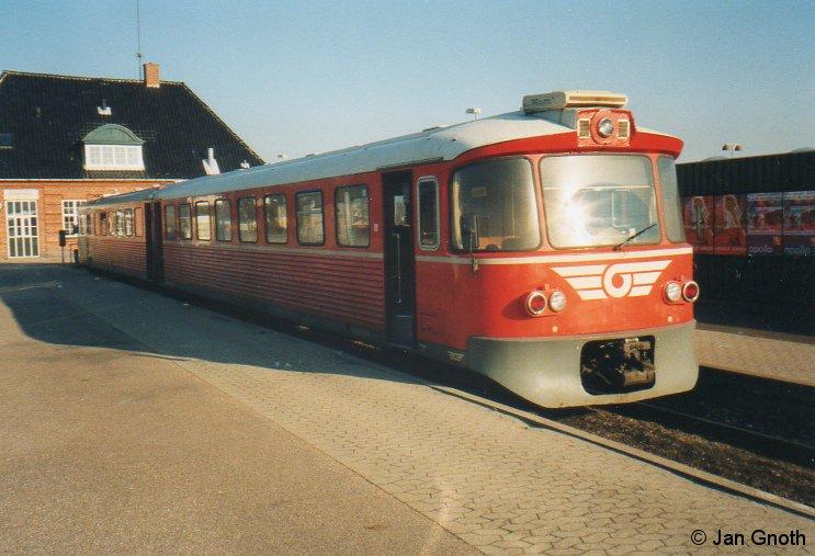 Im Jahre 2002 wurden die Gribskovbahn und die Helsingør-Hornbæk-Gilleleje-Bahn HHGB sowie einige weitere nördlich von Kopenhagen gelegene Privatbahnen zu der Dachgesellschaft Lokalbanen zusammen geschlossen. Betrieblich war davon zunächst noch nichts zu sehen, die zu diesem Zeitpunkt bei allen davon betroffenen Bahnen vorhandenen Fahrzeuge fuhren zunächst auf ihren bisherigen Einsatzstrecken unverändert weiter. So auch dieser hier abgebildete Y-tog der Gribskovbahn, welcher zum Zeitpunkt der Aufnahme im Feburar 2003 in Gilleleje angekommen ist. Dort konnte damals zur Helsingør-Hornbæk-Gilleleje-Bahn HHGB nach Helsingør umgestiegen werden, welche zu diesem Zeitpunkt den selben Zugtyp im Einsatz gehabt hat. Im Jahre 2007 wurden die 1968 angeschafften Y-togene der Baureihe ML durch Alstom Coradia LINT 41 ersetzt und die Strecken der Gribskovbahn Hillerød - Gilleleje und der HHGB Helsingør - Hornbæk - Gilleleje zu einer Strecke durchgebunden, so dass in Gilleleje nicht mehr umgestiegen werden muss.