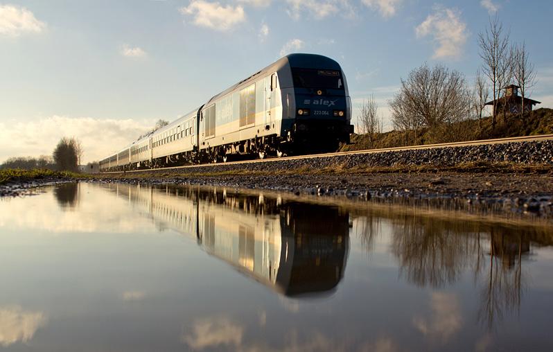 Ein ALEX-Zug spiegelt sich in einer Pfütze bei Geltendorf am 29.01.2016.