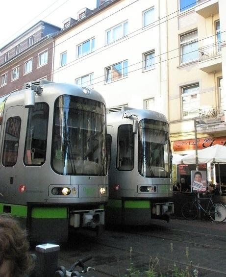 Stadtbahn-Begegnungsverkehr in der Limmerstraße in Linden-Nord. Durch diesen Stadtteil Hannovers führt die Stadtbahnlinie 10, die seit einigen Wochen mit den 2,65m breiten TW2500-Fahrzeugen betrieben wird. Die älteren grünen TW6000-Fahrzeuge waren nur 2,40m breit. Der Anblick, den zwei TW2500 Fahrzeuge bieten, wenn sie sich in der Fußgängerzone Limmerstraße begegnen, wirkt zunächst noch gewaltig und ungewohnt, wird aber jeden Tag mehr und mehr zum Alltag. Auf Außenstehende mag es freilich zunächst erstaunlich wirken, wie hier an einer besonders engen Stelle der Limmerstraße die zwei Stadtbahnfahrzeuge scheinbar die ganze Straßenbreite einnehmen.